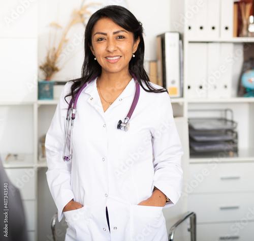 Obraz na plátně Portrait of friendly female doctor wearing white scrubs uniform and stethoscope