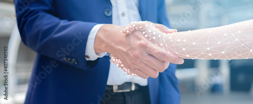 Photo close up on businessman hand shaking with robotic AI hologram to confirm and dea