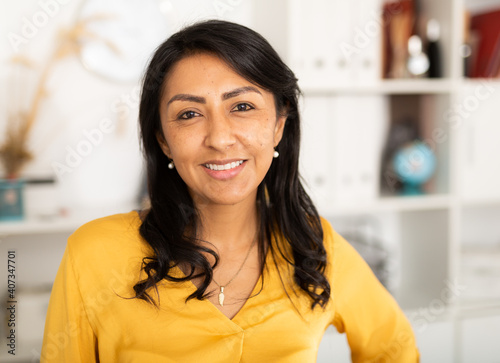 Happy smiling Latin American businesswoman standing in office and looking at cam Poster Mural XXL