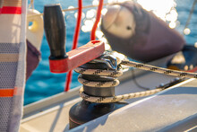 Close Up Of A Winch With Focus On A Rolled Black Striped White Rope. The Jib, Winch Arm, Is Red And Black And Helps To Strength The Sails During Sailing