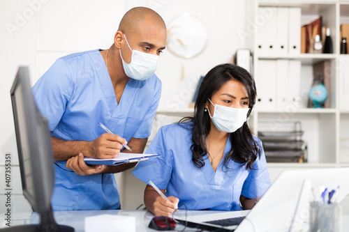 Obraz Doctor and nurse in protective medical mask check patient data in hospital computer database - fototapety do salonu
