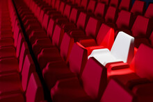 3D Render The Same Rows Of  Red Cartoon Soft Chairs And One White Chair In The Theater. Concept Of A Neon Beautiful Movie Theater With  Chairs