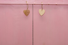 Two Small Hearts Made Of Wood Hang Ropes On Pink Background. Copy Space, Place For Your Text. Valentin's Day Concept, Love, Wedding