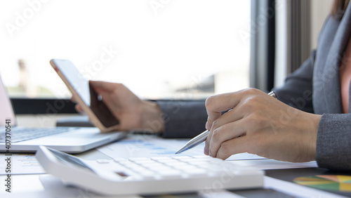 Fototapety, obrazy: Asian female employees are analyzing market data via smartphones and have laptops to calculate the company's finances In a private office at home, Working at home and new normal concept.
