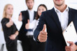 Handsome smiling man showing OK or approval sign with thumb up in creative people office portrait. High level and quality service, job offer, excellent education, advisor, serious business concept
