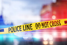 Yellow Law Enforcement Tape Isolating Crime Scene. Blurred View Of City, Toned In Red And Blue Police Car Lights
