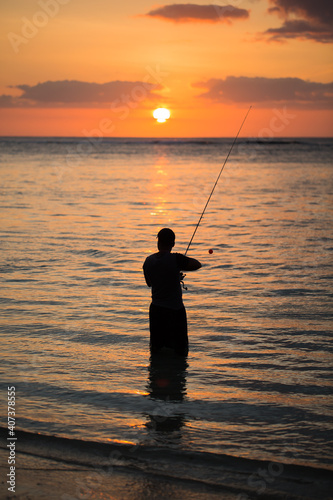Fotografering A man fishing in the Indian ocean with the beach at sunset