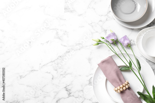 Fotografía Flat lay composition with beautiful dishware and flowers on white marble table