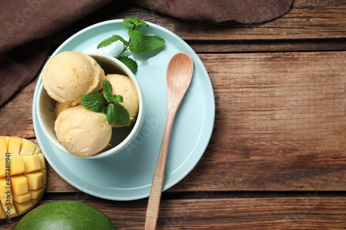 Obraz Delicious mango ice cream served on wooden table, flat lay. Space for text - fototapety do salonu