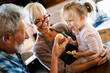 Leinwandbild Motiv Happy grandparents having fun times with children at home