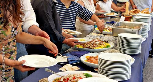 Fototapeta People serving themselves at a buffet, food concept   obraz