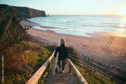 Fototapeta Young woman in casual clothes walk down stairs to beautiful epic beach at sunset or sunrise. Female surfer ready to start surfing lesson at dawn. Millennial lifestyle and hobby obraz