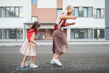 Side View Of A Joyful Little Girl Playing Hopscotch With Her Mother On Playground Outdoors. A Child Plays With Her Mom Outside. A Kid And Mum Play Hopscotch Drawn On The Pavement Outside.