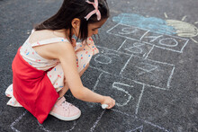 A Cute Little Girl Drawing With Chalk Hopscotch On The Playground. Child Playing The Game Outside. The Kid Wears A Dress During Drawing On The Pavement. Activities And Games For Children Outside.