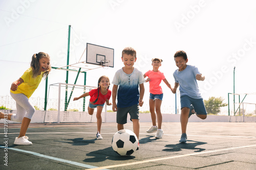 Obraz Cute children playing soccer outdoors on sunny day. Summer camp - fototapety do salonu