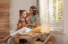 Happy Mother With Little Daughter Near Window At Home