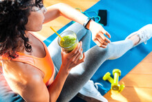 Sporty Woman In Sportswear Training At Home Drinking Fresh Smoothie - Fit Female Athlete Using Smart Watch To Monitor Her Performance - Sport, Food And Technology Concept