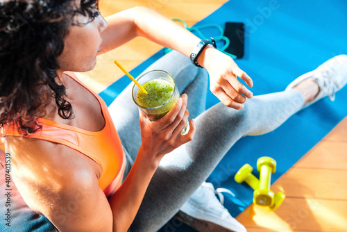 Fototapeta Sporty woman in sportswear training at home drinking fresh smoothie - Fit female athlete using smart watch to monitor her performance - Sport, food and technology concept obraz