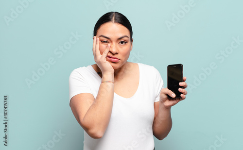 Obraz hispanic woman feeling bored, frustrated and sleepy after a tiresome, dull and tedious task, holding face with hand - fototapety do salonu