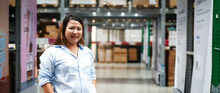 Plus Size Female Worker Inspecting Box Of Products While Working In Large Warehouse