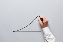 Businessman Hand Drawing A Chart Or Line Graph With An Increasing Slope