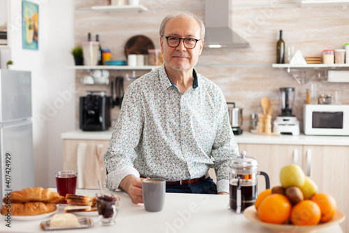 Obraz Mature man with wrinkles looking at camera in modern kitchen enjoying a cup of coffee. Portrait of relaxed elderly senior person in the morning, drinking fresh warm drink, healthy smiling adult face - fototapety do salonu