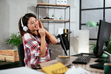 Portrait Of Businesswoman In Office. Beautiful Woman Listening Music At Work..