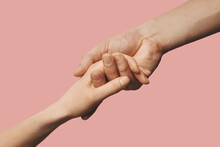 Helping Hand - Support, Assistance And Charity Concept. Hands Reaching Together On Pink Background