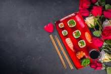 Valentine Day Festive Dinner Idea. Menu, Invitation Background For Valentine Day Sushi Roll Set, With Heart Shaped Decor And Rose Flowers Bouquet. Top View With Copy Space For Text