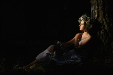 Young Woman Sitting In A Dark Forest