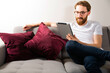 Young adult man using a tablet, a mobile device at home, on a couch.