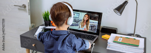 Fotografía Unrecognizable boy with headphones receiving class at home with laptop from his bedroom
