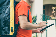 Cropped View Of Deliveryman Looking For House Address And Holding Tablet. Unrecognizable Courier Delivering Order In Thermal Bag And Wearing Red Shirt. Delivery Service And Online Shopping Concept