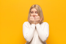 Blonde Woman Looking Worried, Anxious, Stressed And Afraid, Biting Fingernails And Looking To Lateral Copy Space