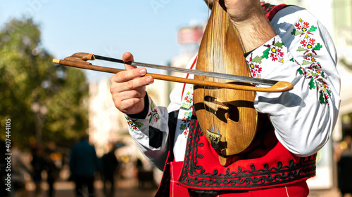 Obraz na plátně Bulgarian folk musician - violinist in traditional national costume plays an old stringed instrument - gadulka on street of Plovdiv city, Bulgaria