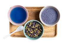 Cup Of Anchan Tea, Matcha Blue Tea Powder And Dried Butterfly Pea Flowers On Wooden Tray Isolated On White. Blue Herbal Tea. Top View