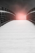 Snow Covered Bridge With Red Glow And Clouds On The Other Side