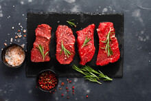 Beef Meat. Four Fresh Raw Beef Steak With Spices, Onions And Rosemary On Dark Slate Or Concrete Background. Top View.