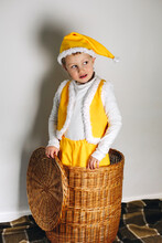 Cute Baby Boy In Yellow Ghome Elf Cap, Vest And Pants Stand Up From Straw Storage Basket, Winter Holidays, Cozy Home