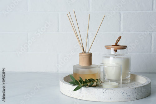 Candles, eucalyptus branch and aromatic reed air freshener on white table near brick wall, space for text. Interior elements © New Africa