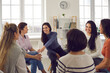 canvas print picture - Happy positive smiling female coach, therapist or business team manager supporting and motivating young women in group therapy session or corporate staff training meeting at work