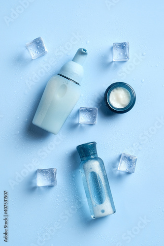 Set of skin moisturizing cosmetics. Face lotion, cream, essential oil on blue background with ice cubes. Flat lay, top view. Water based beauty products.