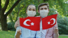 Two Young People Are Waving The Turkish Flag While Looking At The Camera. They Wear A Medical Mask To Protect Them From The Virus.