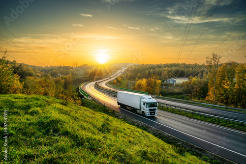 Fotografija White truck driving on the highway winding through forested landscape in autumn