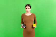 Apple And A Heap Of Pills In Pregnant Woman's Hands At Colorful Background With Copy Space. Making A Choice During Pregnancy Concept