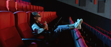 Cheerful Young Woman In 3d Glasses Laughing, Putting Her Feet On A Seat, Holding A Drink While Watching Movie Alone In Empty Cinema Auditorium