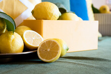 Organic Fresh Juicy Lemons In A Gold Plate And Yellow Box With Yellow, Green, And Blue Background