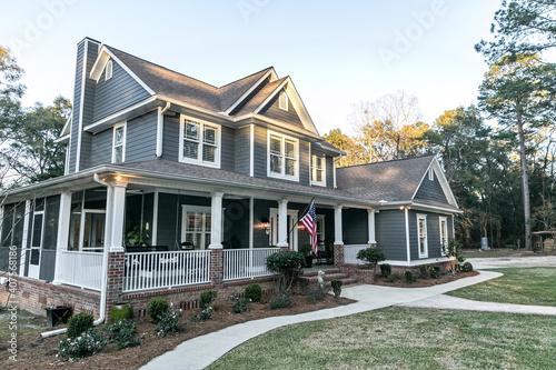 Front view of a large two story blue gray house with wood and vinyl siding - fototapety na wymiar