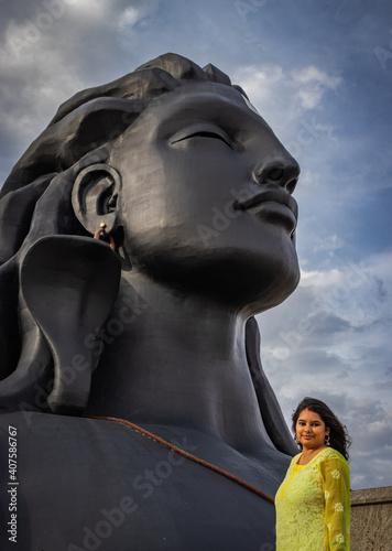 Fotografie, Obraz adiyogi lord shiva statue with young girl in salutation