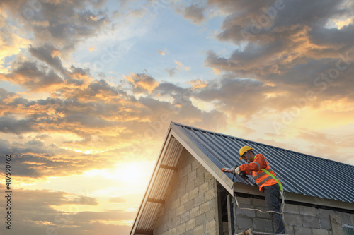 Tablou Canvas Roofer Construction worker install new roof,Roofing tools,Electric drill used on new roofs with Metal Sheet
